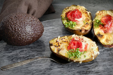 Keto diet dish: Avocado boats with crunchy bacon, melted cheese and cress sprouts on gray stone