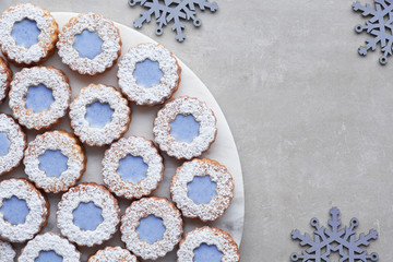 White and blue flower Linzer cookies on light stone background decorated with blue snowflakes