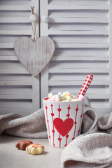 Hot chocolate with marshmallows, red heart on the cup on the table with winter decorations