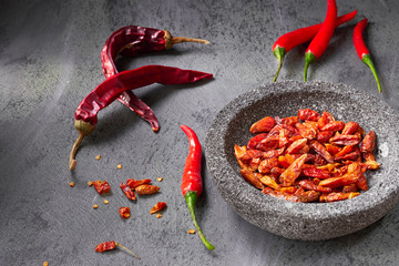 Closeup on  fresh hot chili peppers on dark textured table and dry ones in stone bowl