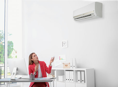 Young woman suffering from heat under broken air conditioner in office