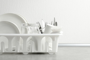 Drying rack with clean dishes and cutlery on table near white wall. Space for text