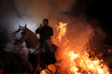 """A man points a phone to himself riding a horse through flames during the annual """"Luminarias"""" celebration northwest of Madrid"""