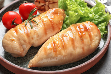 Plate with grilled chicken breasts and garnish on table, closeup