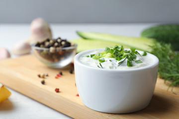 Ceramic bowl of cucumber sauce with ingredients on wooden table, space for text. Traditional Tzatziki