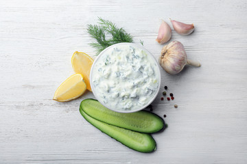 Tzatziki cucumber sauce with ingredients on wooden background, flat lay