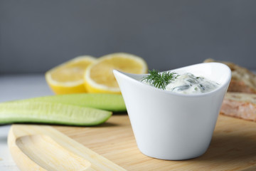 Ceramic bowl of cucumber sauce with ingredients on wooden board, space for text. Traditional Tzatziki