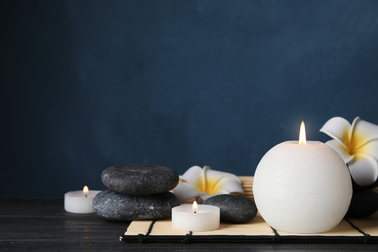 Spa stones, candles and flowers on table, space for text