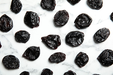 Flat lay of dried plums on marble background. Healthy fruit