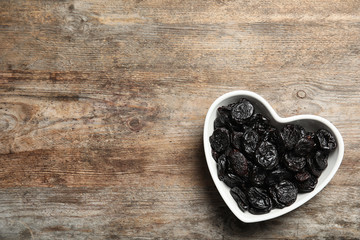Heart shaped bowl of sweet dried plums on wooden background, top view with space for text. Healthy fruit