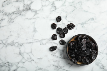 Plate of sweet dried plums on marble background, top view with space for text. Healthy fruit