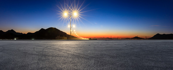 Asphalt road ground and bright street lights landscape at sunset,panoramic view