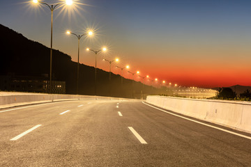 City road and bright street lights landscape at sunset Fotomurales