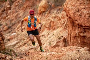 A man Runner of Trail . and athlete's feet wearing sports shoes for trail running in the mountains Wall mural