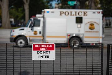 """Restricted area """"Do not enter"""" sign on blurred US secret service uniformed division Police truck parked background"""