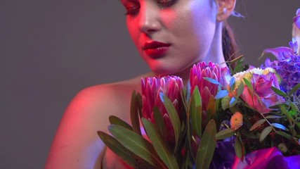Fotoväggar - Sexy brunette model girl with bouquet of beautiful flowers. Beauty young woman with bunch of flowers in colorful neon lights. Art design. Slow motion 4K UHD video footage. 3840X2160