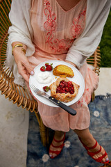 Woman eating Strawberry rhubarb tart with plate on lap