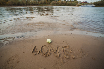 The inscription on the sand is love. The sea and the beach.