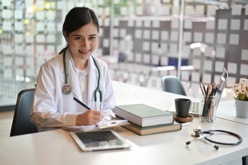 Woman doctor working with report paper in office hospital.