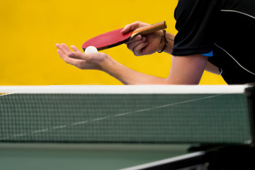 table tennis player serving, focus at ball/blade