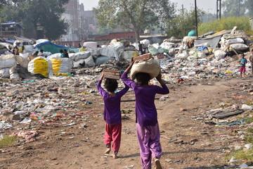 インドの首都のデリー 線路沿いのスラム レンガを頭に乗せて運ぶ少女