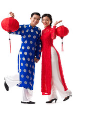 Happy young Asian couple in traditional dresses dancing with paper lanterns