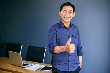 Happy mature Asian businessman showing thumbs-up and looking at camera