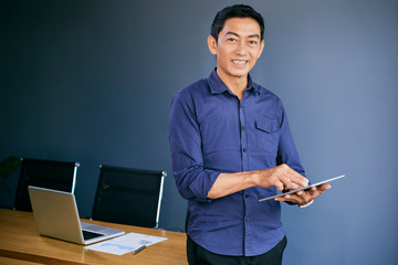 Cheerful Vietnamese businessman working on tablet computer