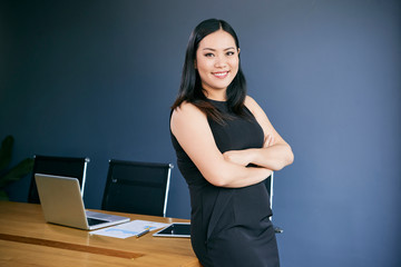 Portrait of cheerful Asian businesswoman with her arms folded