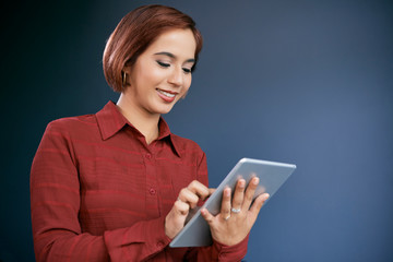 Smiling Asian business lady checking document on tablet computer