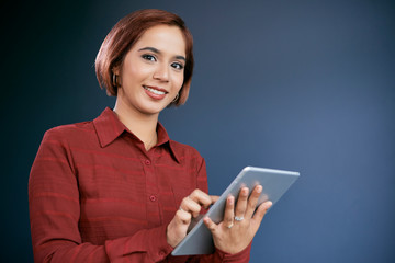 Pretty smiling businesswoman working on digital tablet and looking at camera