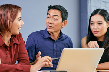 Asian businessman listening to idea of his female coworker at meeting