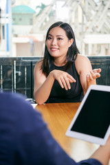 Pretty smiling young businesswoman talking to coworkers at meeting