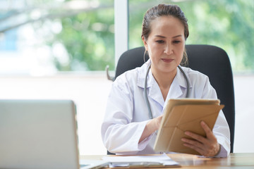 Mature Vietnamese general practitioner reading information on tablet computer