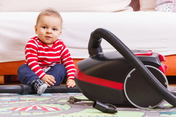 Happy little baby boy sitting on carpet and playing with pipe of vacuum cleaner