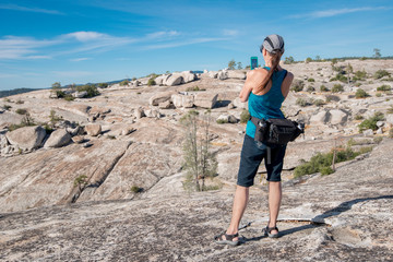 Older, woman hiker in rocky landscape taking picture on cell phone