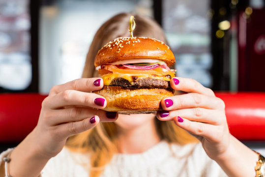 Young girl holding in hands fast food burger with cutlet, cheese and red onion.