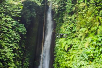 Little quadcopter flying around waterfall Leke Leke Bali island Indonesia