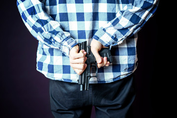 robber pull out pistol behind his back. crime and robbery concept b