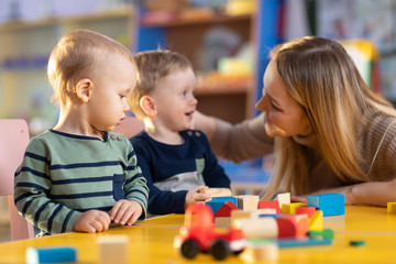 nursery children building blocks with a teacher in preschool playroom