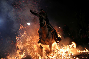 """A woman rides a horse through flames during the annual """"Luminarias"""" celebration northwest of Madrid"""