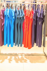 Women's dresses hang on hangers in a women's clothing store.