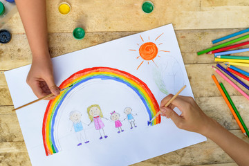 Two children's hands draw a drawing with a brush and paints. Top