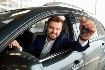 Male driver smiling holds the keys to the car