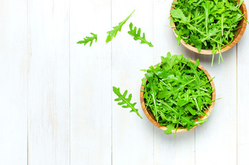 Fresh green arugula leaves on wooden bowl, rucola salad on white wooden rustic background top view with place for text. Rocket salad or arugula, healthy food, diet. Nutrition concept.