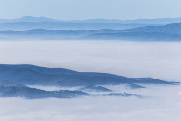 Fog filling a valley in Umbria (Italy), with layers of mountains and hills and various shades of blue