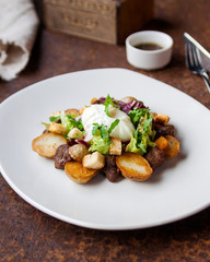 Warm salad with chicken, grilled potatoes, crackers, arugula, grated cheese and poached egg on a white plate and soy dressing. Close up. Selective focus. The concept of the menu.