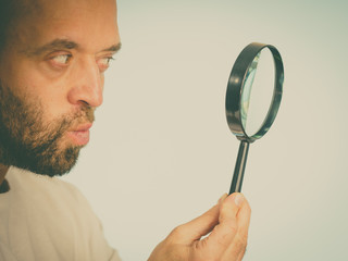 Curious man using magnifying glass