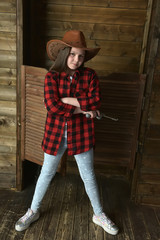 girl cowboy in a red checkered shirt on the background of a wooden wall
