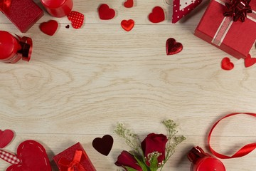 Gift boxes, rose and heart shape decorations on wooden table